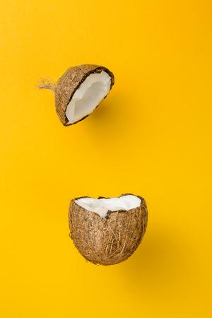 Kokosnoot op gele gekleurde achtergrond, minimale vlakke lay-stijl
