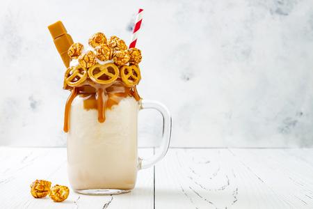 Salted caramel indulgent exreme milkshakes with brezel waffles, popcorn and whipped cream 스톡 콘텐츠