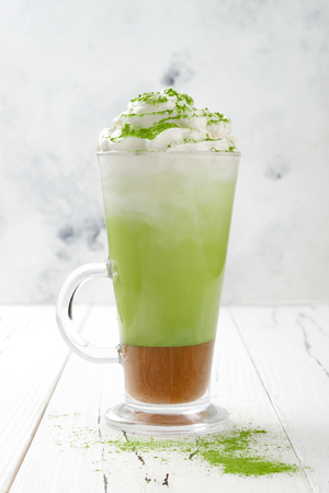 Matcha latte with salted caramel in tall glass.