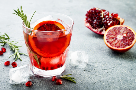 Red cocktail with blood orange and pomegranate. Refreshing summer drink on gray stone or concrete background 스톡 콘텐츠
