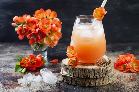 Floral pastel peach and pink brunch cocktail garnished with quince flowers over old rustic background. Imagens
