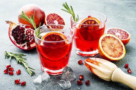 빨간색 혈액 오렌지와 석류 칵테일입니다. 회색 돌 또는 콘크리트 배경에 여름 음료를 상쾌. 크리스마스 파티를위한 휴일 아페리티프.
