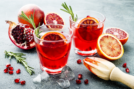 Red cocktail with blood orange and pomegranate. Refreshing summer drink on a gray stone or concrete background. Holiday aperitif for Christmas party.