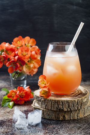 Floral pastel peach and pink brunch cocktail garnished with quince flowers over old rustic background. Stok Fotoğraf