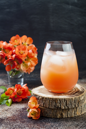 Floral pastel peach and pink brunch cocktail garnished with quince flowers over old rustic background. Stock Photo