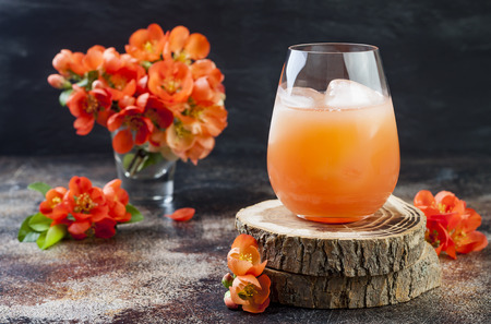 Floral pastel peach and pink brunch cocktail garnished with quince flowers over old rustic background. 스톡 콘텐츠