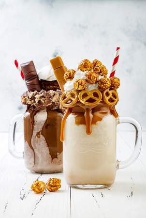 Caramel and chocolate indulgent exreme milkshakes with brezel waffles, popcorn, marshmallow, ice cream and whipped cream 版權商用圖片