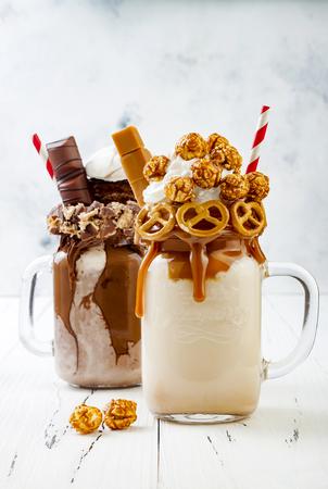 Caramel and chocolate indulgent exreme milkshakes with brezel waffles, popcorn, marshmallow, ice cream and whipped cream Standard-Bild