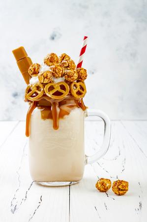 Gezouten karamel toegeeflijke exreme milkshakes met brezelwafels, popcorn en slagroom