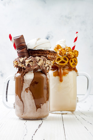 Caramel and chocolate indulgent exreme milkshakes with brezel waffles, popcorn, marshmallow, ice cream and whipped cream Banco de Imagens
