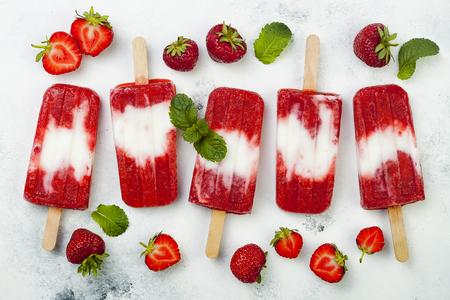 Homemade vegan strawberry coconut milk popsicles - ice pops - paletas on rustic white background