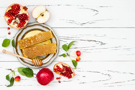 Apple, pomegranate and honey, traditional food of jewish New Year - Rosh Hashana. Copy space background