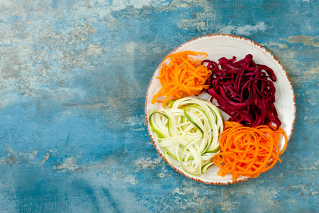 Zucchini, carrot, sweet potato and beetroot noodles on a plate. Top view, overhead, copy space. Blue rustic background