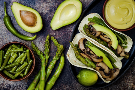 Grilled portobello, asparagus, bell peppers, green beans fajitas. Poblano mushroom tacos with jalapeno, cilantro, avocado crema. Vegan tacos with green summer vegetables. Stock Photo