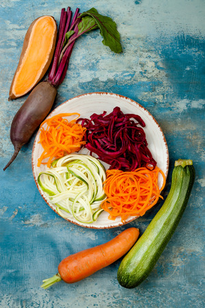 Zucchini, carrot, sweet potato and beetroot noodles on a plate. Top view, overhead. Blue rustic background Stock Photo