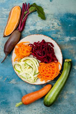 Zucchini, Karotten, Süßkartoffel und Rote Beete Nudeln auf einem Teller. Draufsicht, Overhead. Blauer rustikaler Hintergrund Standard-Bild - 84082292