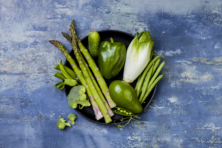 Green veggies group on a tray. Vegetarian dinner ingredients. Green vegetables variety. Overhead, flat lay, top view, copy space