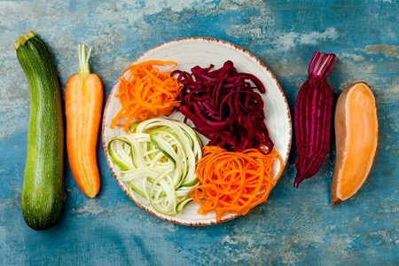Zucchini, carrot, sweet potato and beetroot noodles on a plate. Top view, overhead. Blue rustic background Zdjęcie Seryjne