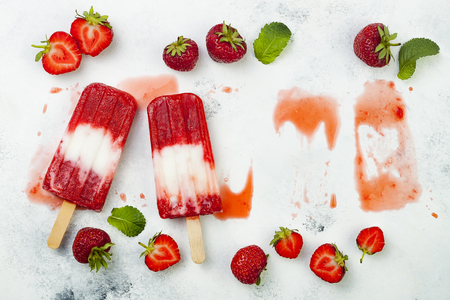 Homemade vegan strawberry coconut milk popsicles - ice pops - paletas on rustic white background. Copy space