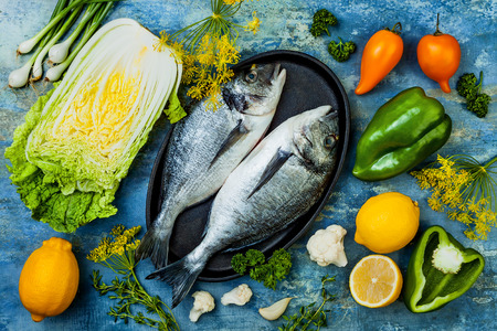 Dorado in baking form ready to cooking, preparation on rustic blue background with fresh vegetables, herbs and spices. Top view, overhead Stock Photo