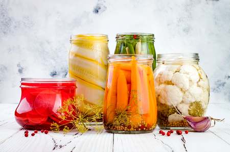 Marinated pickles variety preserving jars. Homemade green beans, squash, radish, carrots, cauliflower pickles. Fermented food. Reklamní fotografie