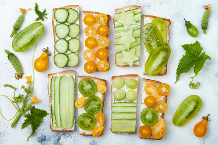 Green and yellow vegetables sandwiches. Variety of sandwiches with cream cheese, cucumbers and tomatoes on a light background. Top view, flat lay, overhead