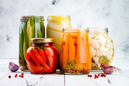 Marinated pickles variety preserving jars. Homemade green beans, squash, cauliflower, carrots, red chili peppers pickles. Fermented food. Stock Photo