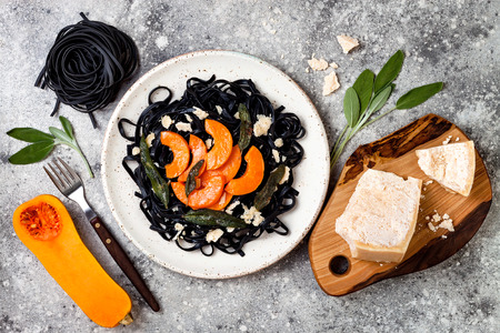 Black pasta with roasted butternut squash, parmesan cheese and fried sage. Concrete background, top view, flat lay. Halloween black and orange party dinner concept