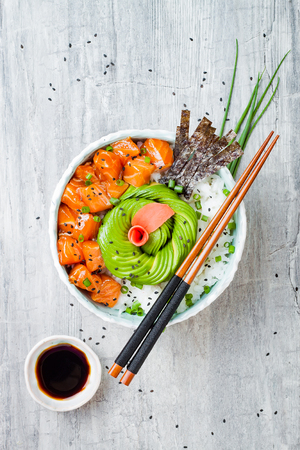 Hawaiian salmon poke bowl with seaweed, avocado rose, sesame seeds and scallions. Top view, overhead, flat lay, copy space