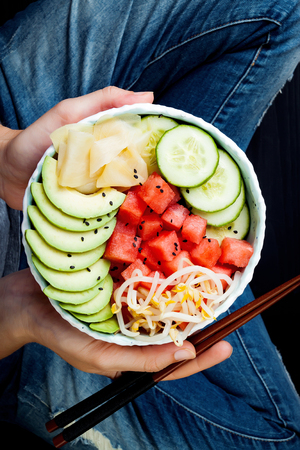 Girl in jeans holding hawaiian watermelon poke bowl with avocado, cucumber, mung bean sprouts and pickled ginger. Top view, overhead Stock Photo