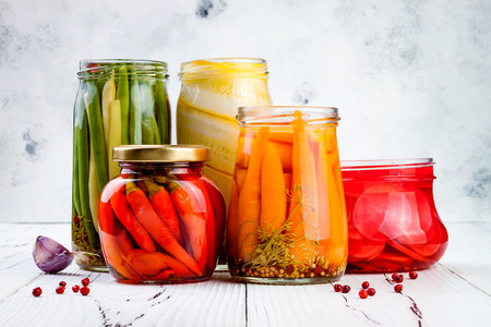 Marinated pickles variety preserving jars. Homemade green beans, squash, radish, carrots, red chili peppers pickles. Fermented food.