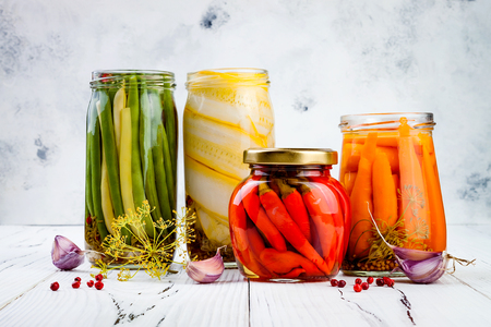 Marinated pickles variety preserving jars. Homemade green beans, squash, carrots, red chili peppers pickles. Fermented food.