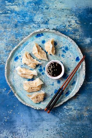 醤油、胡麻、お箸を持つアジアの餃子。伝統的な中国点心餃子。空間、フラット レイアウトをコピーします。