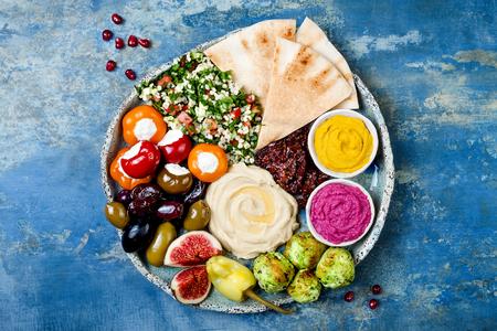 緑ファラフェル、ピタ、サンドライ トマト、カボチャ、ビートのフムス、オリーブ、ピーマン、タブレ、イチジクと中東のメゼの盛り合わせ。地中