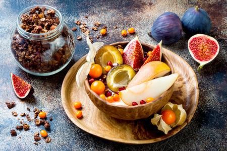 Fall breakfast bowl with chocolate granola, coconut yogurt and autumn seasonal fruits and berries. Healthy vegan, vegetarian breakfast table