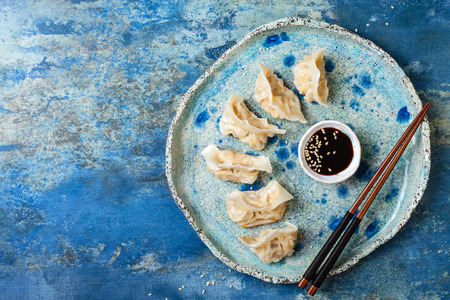 Asian dumplings with soy sauce, sesame seeds and chopsticks. Traditional chinese dim sum dumplings. Copy space, flat lay