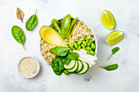 Vegan, detox green Buddha bowl recipe with quinoa, avocado, cucumber, spinach, tomatoes, mung bean sprouts, edamame beans, daikon radish. Top view, flat lay