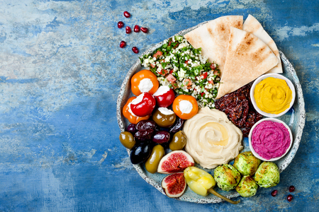 Middle Eastern meze platter with green falafel, pita, sun dried tomatoes, pumpkin and beet hummus, olives, stuffed peppers, tabbouleh, figs. Mediterranean appetizer party idea