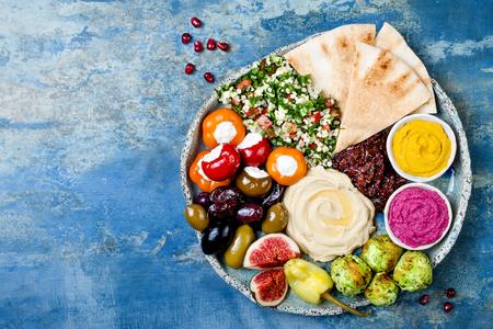 Midden-Oosterse mezeschotel met groene falafel, pita, zongedroogde tomaten, pompoen en bietenhummus, olijven, gevulde paprika's, tabouleh, vijgen. Mediterraan voorgerecht partij idee