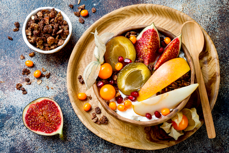 Fall breakfast bowl with chocolate granola, coconut yogurt and autumn seasonal fruits and berries. Healthy vegan, vegetarian breakfast table