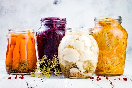 Sauerkraut variety preserving jars. Homemade red cabbage beetroot kraut, turmeric yellow kraut, marinated cauliflower and carrots pickles. Fermented food.