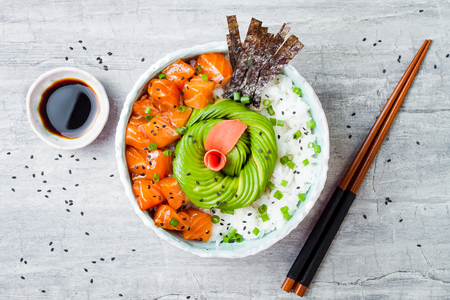Hawaiian salmon poke bowl with seaweed, avocado rose, sesame seeds and scallions. Top view, overhead, flat lay