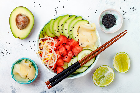 Vegan watermelon poke bowl with avocado, cucumber, mung bean sprouts and pickled ginger. Top view, overhead, flat lay Stock Photo