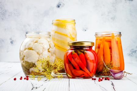 Gemarineerde augurken voor het behoud van variëteiten. Huisgemaakte bloemkool, squash, wortels, rode chilipepers. Gefermenteerd voedsel. Stockfoto