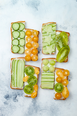 Green and yellow vegetables open faced sandwiches. Variety of sandwiches with cream cheese, cucumbers and tomatoes on a light background. Top view, flat lay, overhead