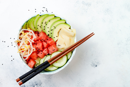 Hawaiian watermelon poke bowl with avocado, cucumber, mung bean sprouts and pickled ginger. Top view, overhead, flat lay, copy space Stock Photo