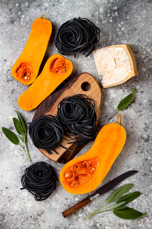 버터 넛 스쿼시, 파르 메산 치즈와 현자로 검은 파스타를 만들기위한 원료. 콘크리트 배경, 상위 뷰, 평면 누워. 할로윈 검은 색과 오렌지색 파티 저녁  스톡 콘텐츠