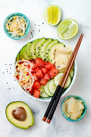 Hawaiian watermelon poke bowl with avocado, cucumber, mung bean sprouts and pickled ginger. Top view, overhead, flat lay