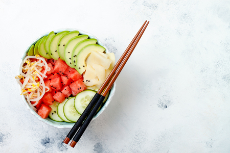 bean sprouts: Hawaiian watermelon poke bowl with avocado, cucumber, mung bean sprouts and pickled ginger. Top view, overhead, flat lay, copy space Stock Photo
