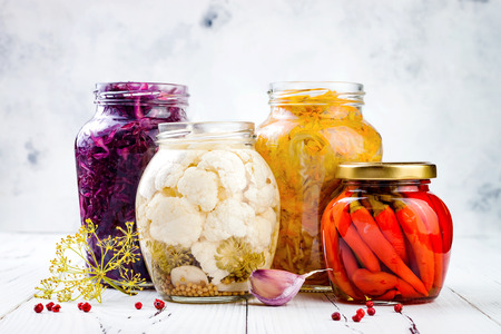 Sauerkraut variety preserving jars. Homemade red cabbage beetroot kraut, turmeric yellow kraut, marinated cauliflower, red chili peppers pickles. Fermented food. Archivio Fotografico